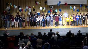 students hold balloons on stage