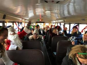 teachers on board a bus called the holly jolly express