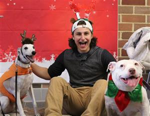 student poses with therapy dogs